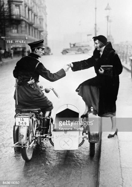 Une Berlinoise monte dans le sidecar du gardien qui la ramènera à son domicile grâce à ce nouveau systèmpe de sécurité selon lequel toutes les femmes...
