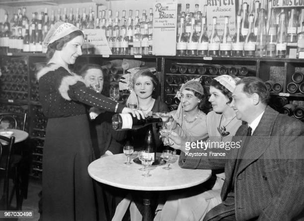 Une catherinette versant à boire à ses camarades à Paris France le 25 novembre 1933