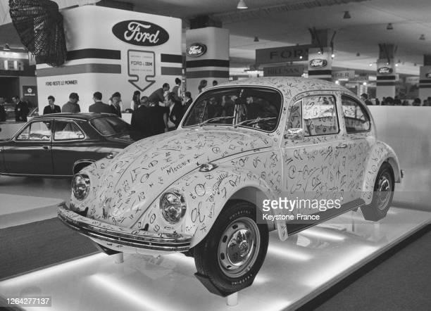 Une Coccinelle Volkswagen sur laquelle chaque vérification de pièces a été notée sur la carrosserie est exposée au Salon de l'Auto le 2 octobre 1969...