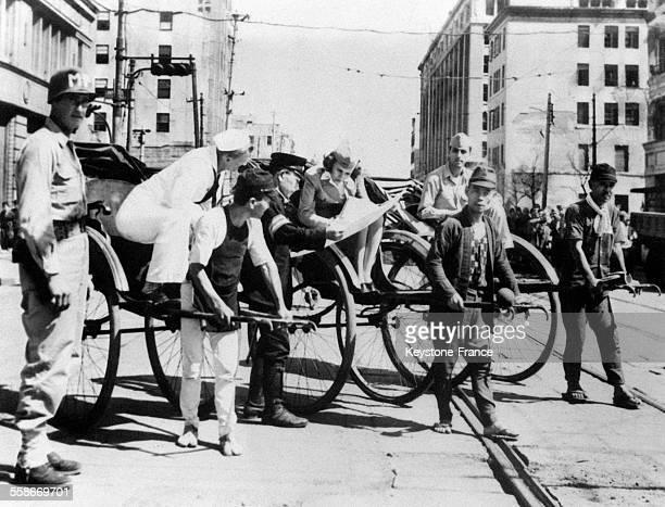 Une dame de la CroixRouge américaine un marin et un GI se font promener en poussepousse dans les rues de la capitale et demandent leur chemin à un...