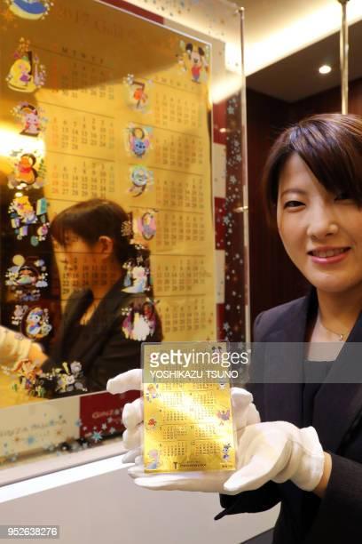 Une employée de la bijouterie japonaise Tanaka Kikinzoku présente au public un calendrier avec des peersonnages Disney en or massif de 125 kg sa...