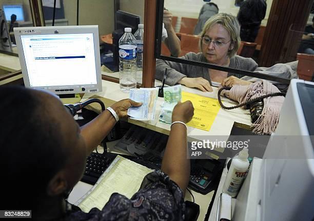 Une employée du Crédit Municipal remet de l'argent à une personne ayant déposé des objets de valeur à l'établissement, le 13 octobre 2008 à Paris....