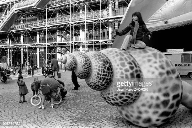 Une enfant joue assise sur une sculpture représentant un coquillage sous le regard envieux de d'autres enfants dans le quartier de Beaubourg le 3...