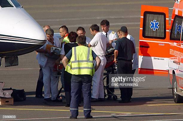 Une equipe de medecins du SAMU francais transfere Marie Trintignant en etat de coma depasse dans un avion sanitaire le 31 juillet 2003 sur l'aeroport...
