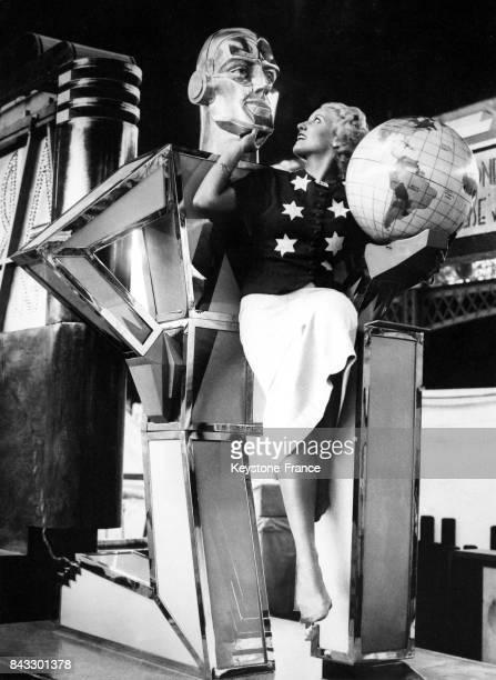 Une femme admire la sculpture en verre représentant un homme au stand de Marconi à Londres RoyaumeUni en août 1935