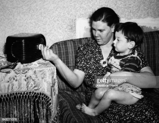 Une femme assise sur son canapé son enfant sur les genoux tourne le bouton d'un poste de radio