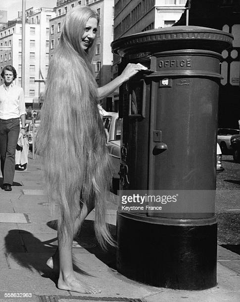 Une femme aux très longs cheveux qui la couvrent presque entièrement poste une lettre