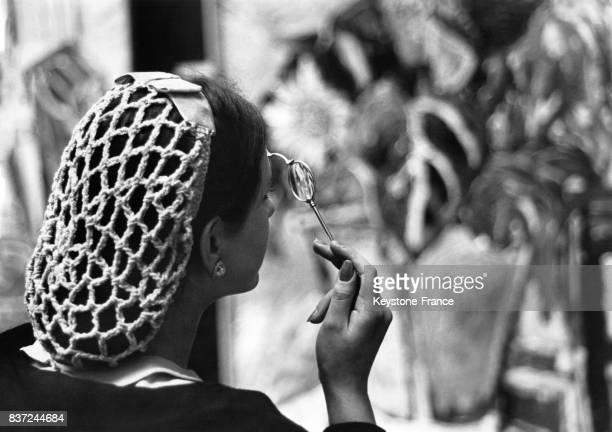 Une femme dont les cheveux sont couverts d'un filet munie d'un lorgnon observe les oeuvres de la Royal Academy lors d'une visite privée le 30 avril...