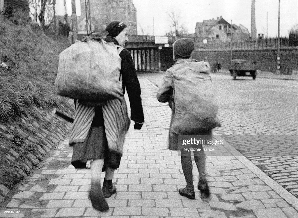 une femme et un enfant portant chacun un sac rempli de. Black Bedroom Furniture Sets. Home Design Ideas