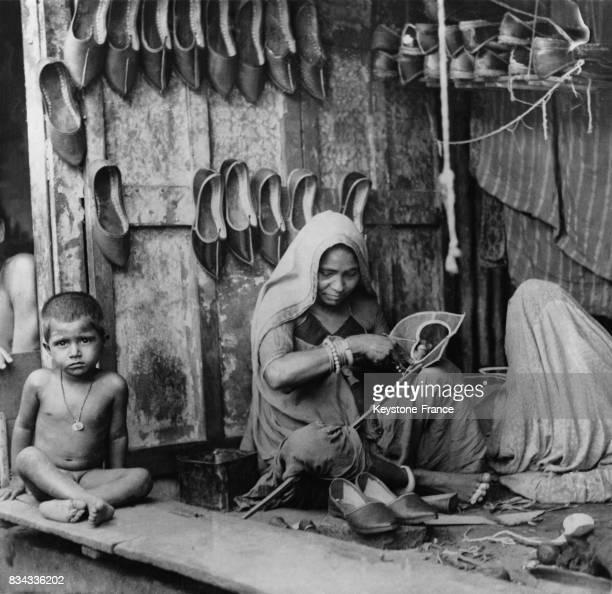 Une femme fabrique des chaussures en cuir dans une échoppe en Inde