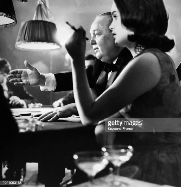Une femme fume une cigarette le visage tendu à côté d'autres joueurs à la table de jeu dans le casino d'un club privé de Grosvenor Square lancé par...