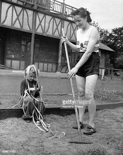 Une femme égalise le gravier de la cour avec un rateau pendant que sa fille joue avec des rubans de scotch