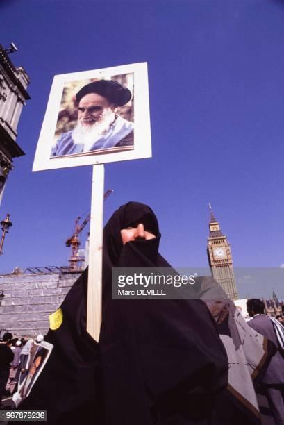 Une femme habillée d'un voile intégral montre une photo de l'ayatollah Khomeini lors d'une manifestation contre l'écrivain Salman Rushdie le 27 mai...