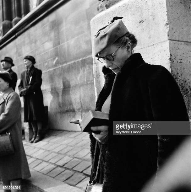 Une femme lit son missel pendant le passage de la procession du Chemin de Croix à SaintPierredeMontmartre à Paris France le 3 avril 1953