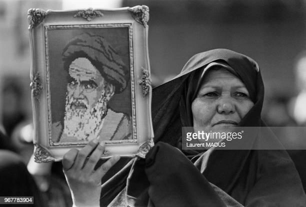Une femme montre un portrait de l'ayatollah Khomeini dans une manifestation le 13 avril 1982 à Téhéran Iran
