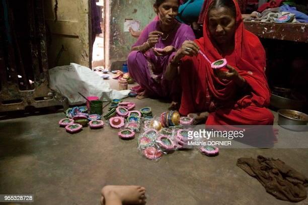 Une femme peint avec précision des diyas dans la seule pièce qui lui sert de maison New Delhi Inde