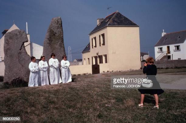 Une femme photographie des communiants en aube sur l'île de Sein en France