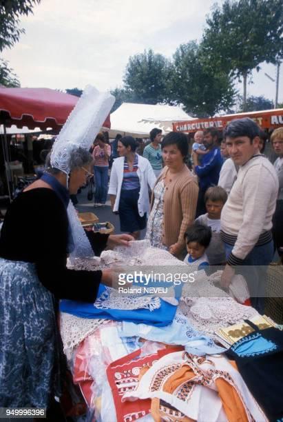 Une femme portant une coiffe bigoudène vendant des articles en dentelle sur un marché en août 1977 à SaintMalo France