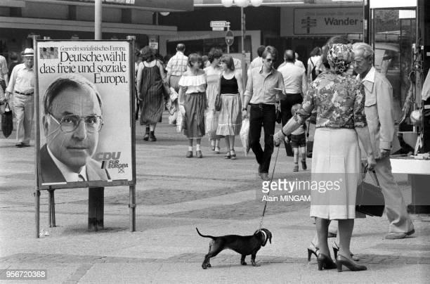 Une femme promène son chien près d'affiche de Helmut Kohl dans une rue de Hanovre lors de la campagne européenne en juin 1979 Allemagne