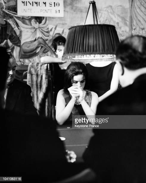 Une femme réfléchit à la carte qu'elle va jouer assise à la table de jeux en face du croupier français du nouveau casino ouvert au River Club de...