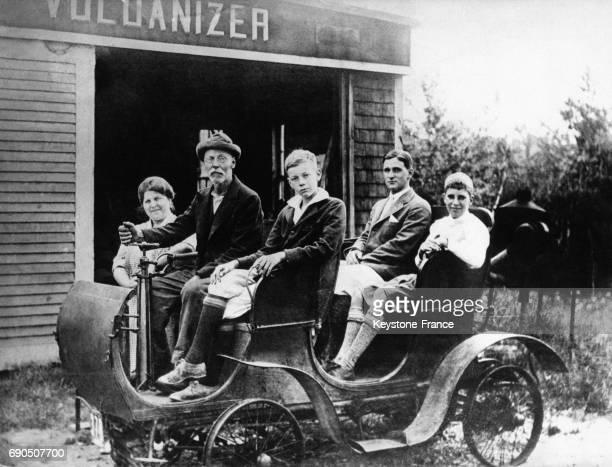 Une femme se tient debout à côté du véhicule les hommes sont assis dans les quatre places de la voiture dans le Maine aux ÉtatsUnis circa 1900