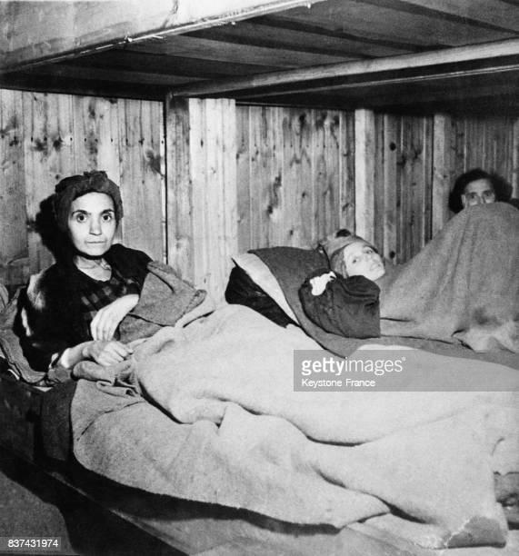 Une femme squeletique le regard effaré repose encore en vie sur un lit à Penig Allemagne en 1945