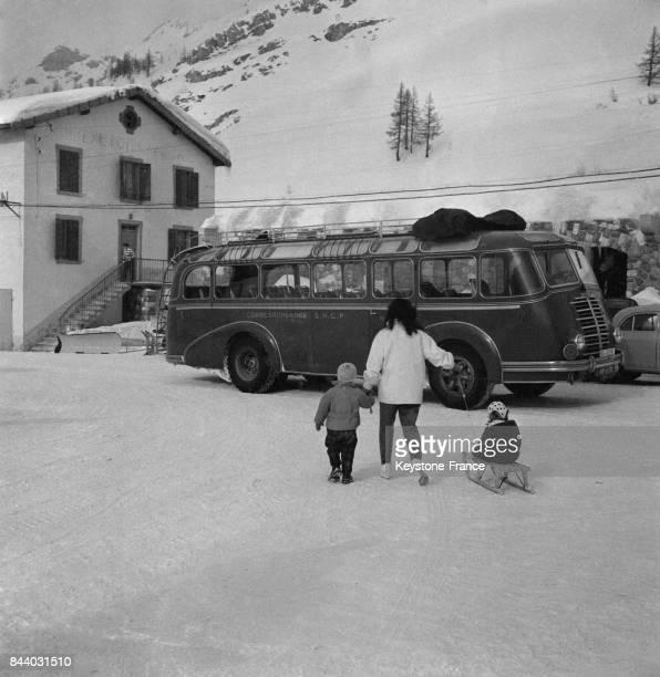 Une femme traîne une luge où son enfant s'est assis au Val d'Isère France en février 1956
