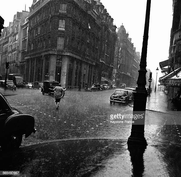 Une femme trempée par la forte pluie et la grêle traverse la rue hors des passages cloutés à LevalloisPerret France le 9 juillet 1956