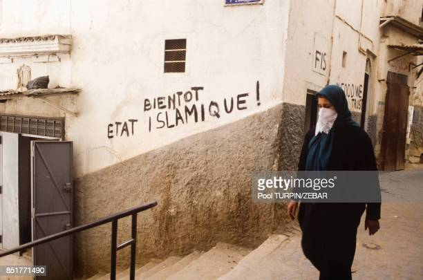 Une femme voilée passe devant un graffiti à la gloire du FIS le 14 février 1992 à Alger Algérie