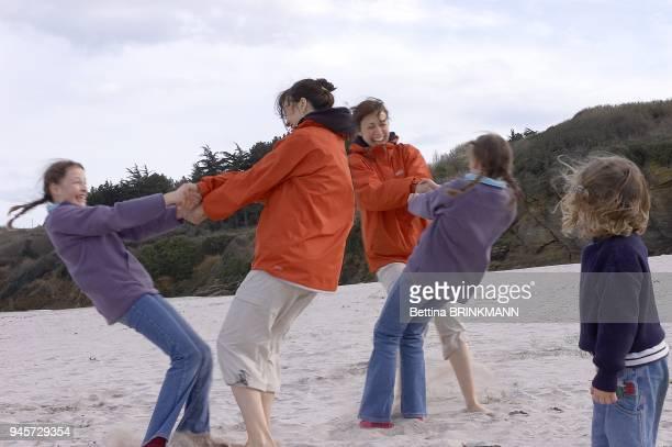 Une fille de 4 ans regarde une adulte qui tourne sur la plage avec une adolescente