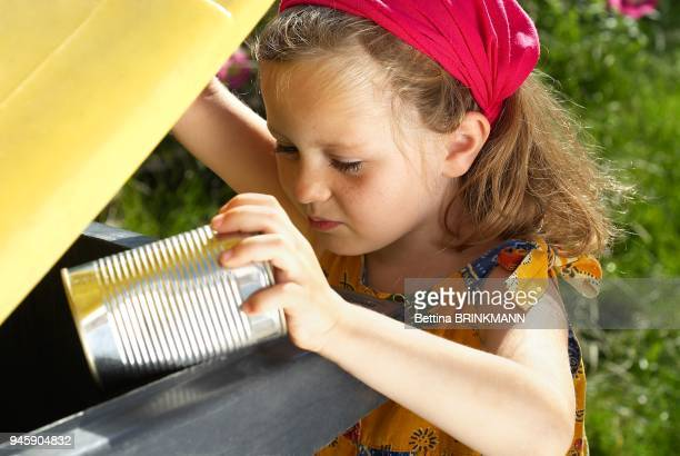Une fille de 5 ans jette une boite de conserve dans la poubelle