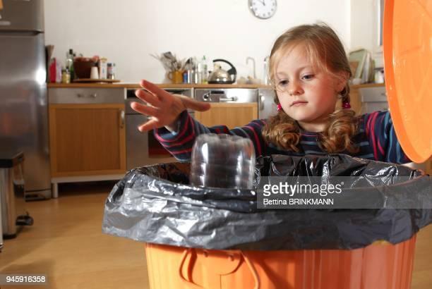 Une fille de 6 ans jette des une bouteille plastique a la poubelle
