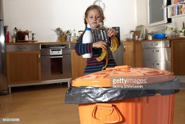Une fille de 6 ans s'avance vers une poubelle des dechets a la main