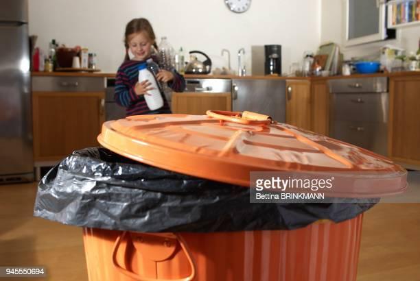 une fille de 6 ans s'avance vers une poubelle trois bouteilles en plastique a la main