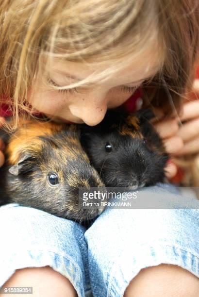 Une fille de 9 ans tient deux cochons d'Inde sur ses genoux