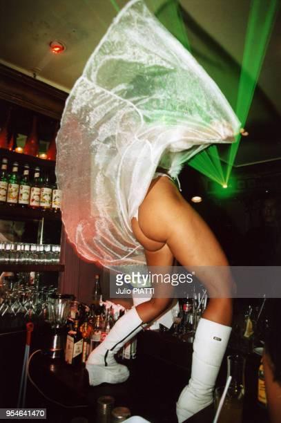 Une gogo danseuse des Bains Douches fait le spectacle juchée sur un comptoir de bar en janvier 2000 à Paris, France.
