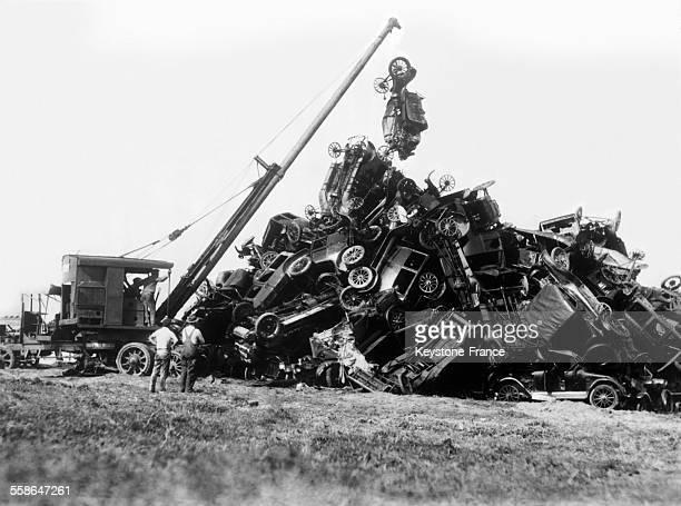 Une grue dépose une carcasse de voiture sur un tas de ferraille dans une casse automobile à Newark New Jersey EtatsUnis le 5 avril 1930