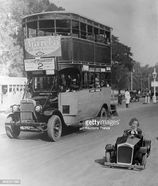 Une jeune Anglaise dans sa voiture la plus petite du monde roule à côté d'un autobus gigantesque à Calcutta Inde le 11 janvier 1935