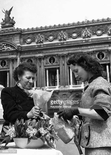 Une jeune femme achète un bouquet de muguet portebonheur à une marchande dans la rue place de l'Opéra le 1er mai 1953 à Paris France