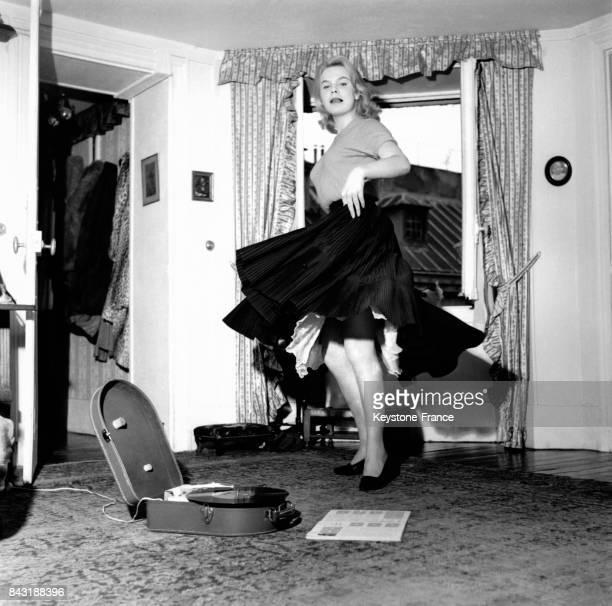 Une jeune femme blonde danse dans son salon au son d'un disque qui tourne sur son tourne-disque, circa 1960.