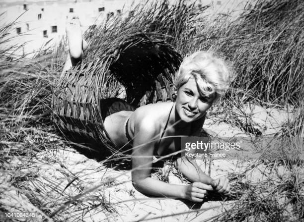 Une jeune femme blonde en maillot de bain dans un anneau en osier au soleil sur la plage d'un île de la Mer du Nord le 2 août 1965 à Juist, Allemagne.