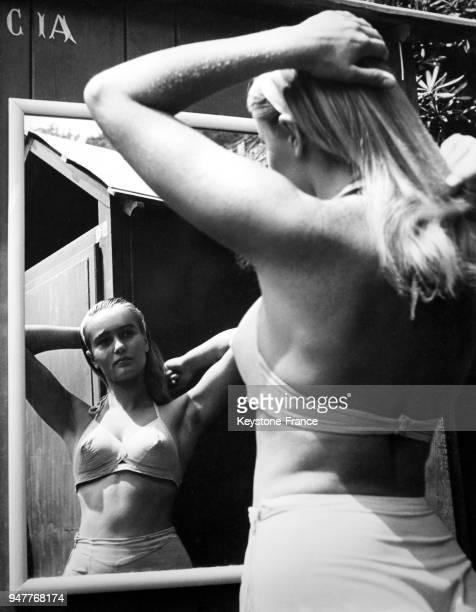 Une jeune femme blonde en maillot de bain se brosse les cheveux devant une glace.