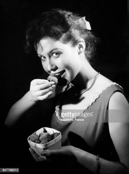 Une jeune femme croque une fraise
