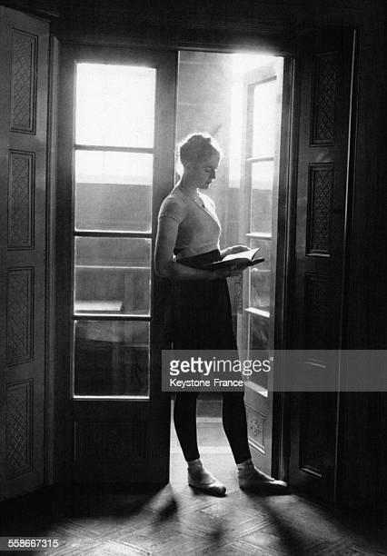 Une jeune femme portant des chaussons de danse lit dans une encadrure de porte