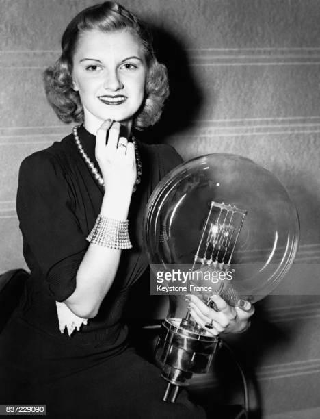 Une jeune femme présente la plus grosse et la plus petite ampoules électriques du monde lors d'une exposition sur l'électricité le 19 avril 1938 à...