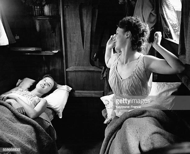 Une jeune femme s'étire tandis que sa compagne de cabine reste au lit le 28 juin 1946