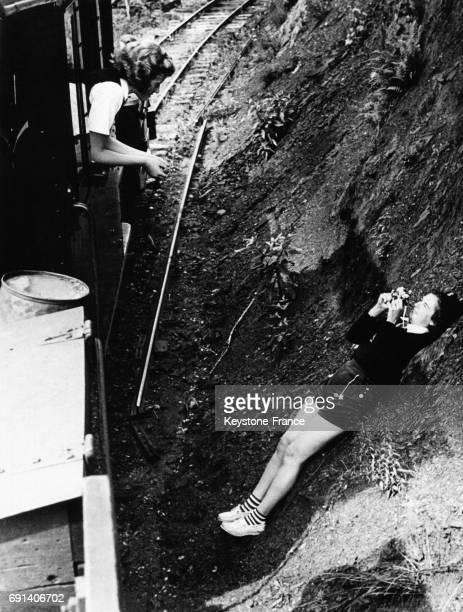 Une jeune fille allongée sur un haut talus prend en photo sous un angle inhabituel une passagère du petit train Tweetsie dans le parc d'attractions...
