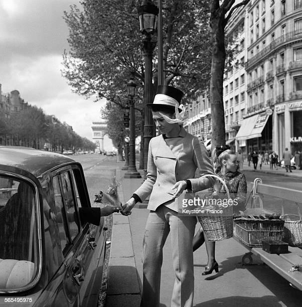 Une jeune fille vendant du muguet à un automobiliste Avenue des Champs Elysées à Paris France le 1 mai 1968