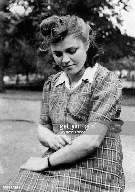 Une jeune juive polonaise, Helen Klein, témoin dans le procès des bourreaux de Belsen, montre les tatouages effectués sur son bras pendant son séjour...