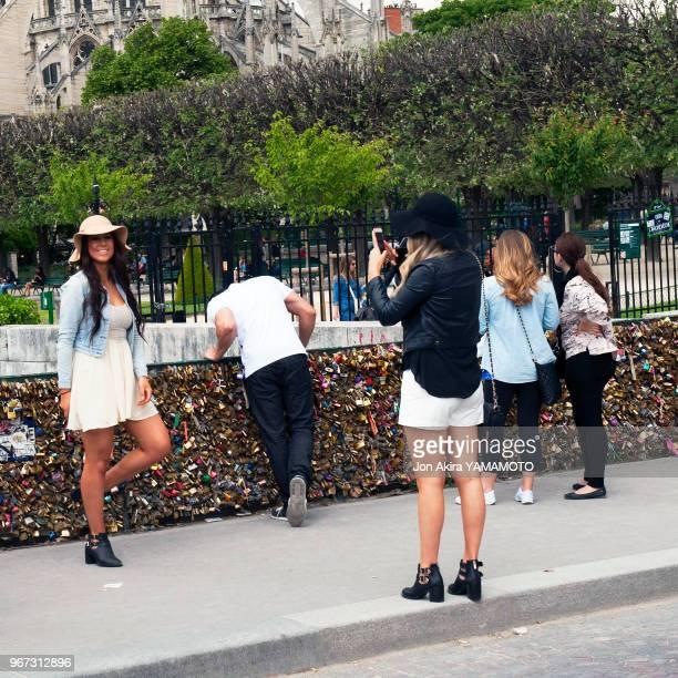 Une jeune touriste pose pour une photo devant les cadenas d'amour sur le Pont de l'Archevêché Paris France